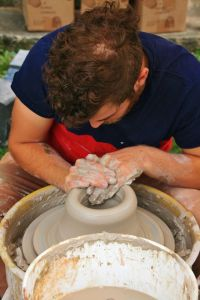 Lou Lourdeau's pottery pics, potter spinning clay