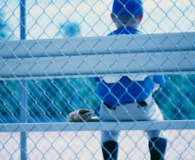 Young Baseball Player Waiting on Sidelines